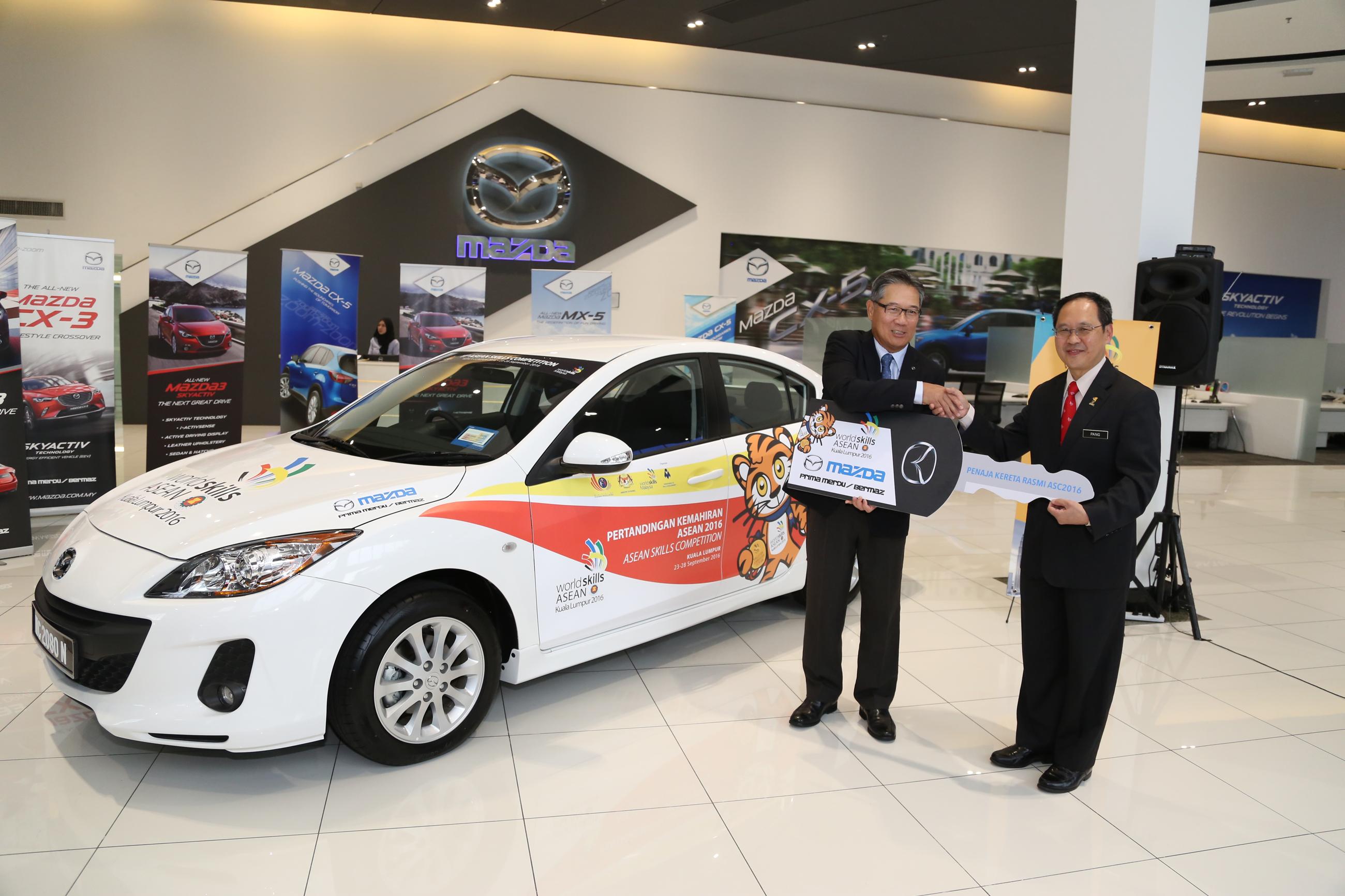 Bermaz Motor managing director Datuk Seri Ben Yeoh handing over a mock Mazda3 car key to Human Resources Ministry Training Development director-general Datuk Dr Pang Chau